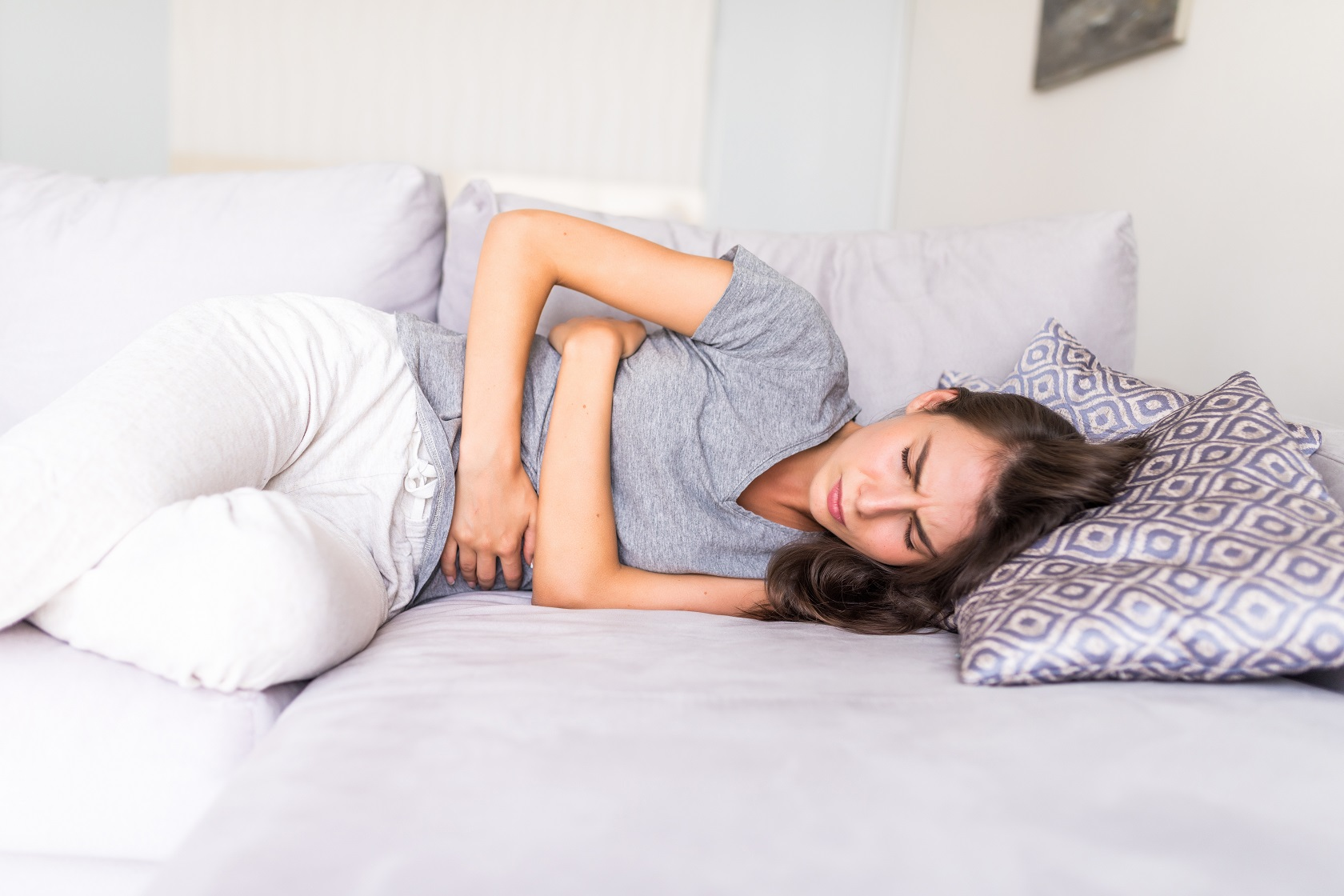 Young woman have abdominal pain because of menstruation lying in couch and holding her stomach.